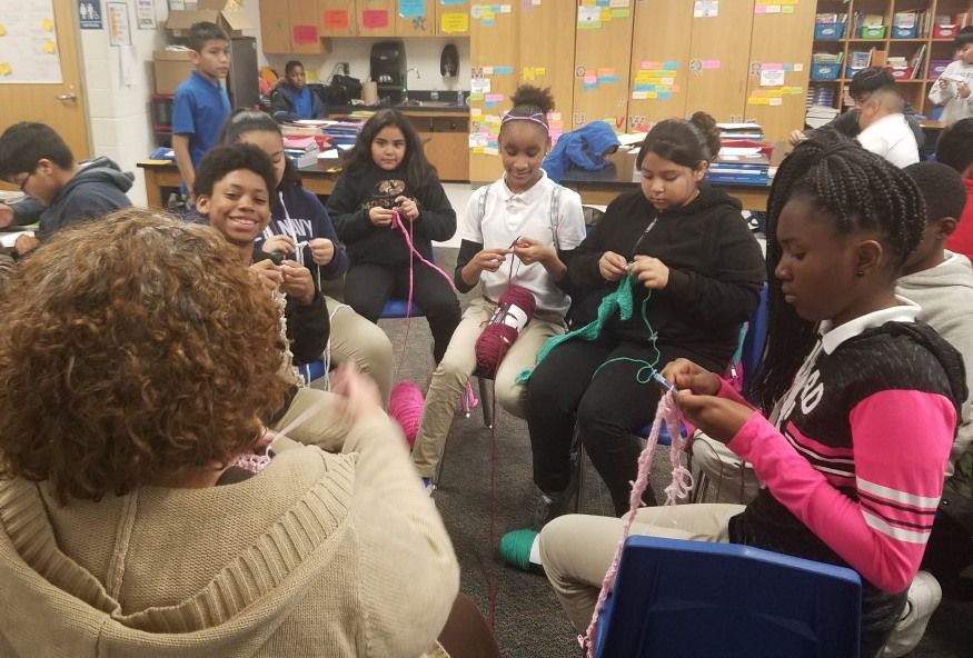 Some of Charlotte Geisler's fifth-grade students at Wilmer-Hutchins Elementary School work on their crochet creations. Geisler often invites the students to spend a portion of their recess learning how to crochet. Once a month, Geisler collects their work and donates it to local homeless shelters.