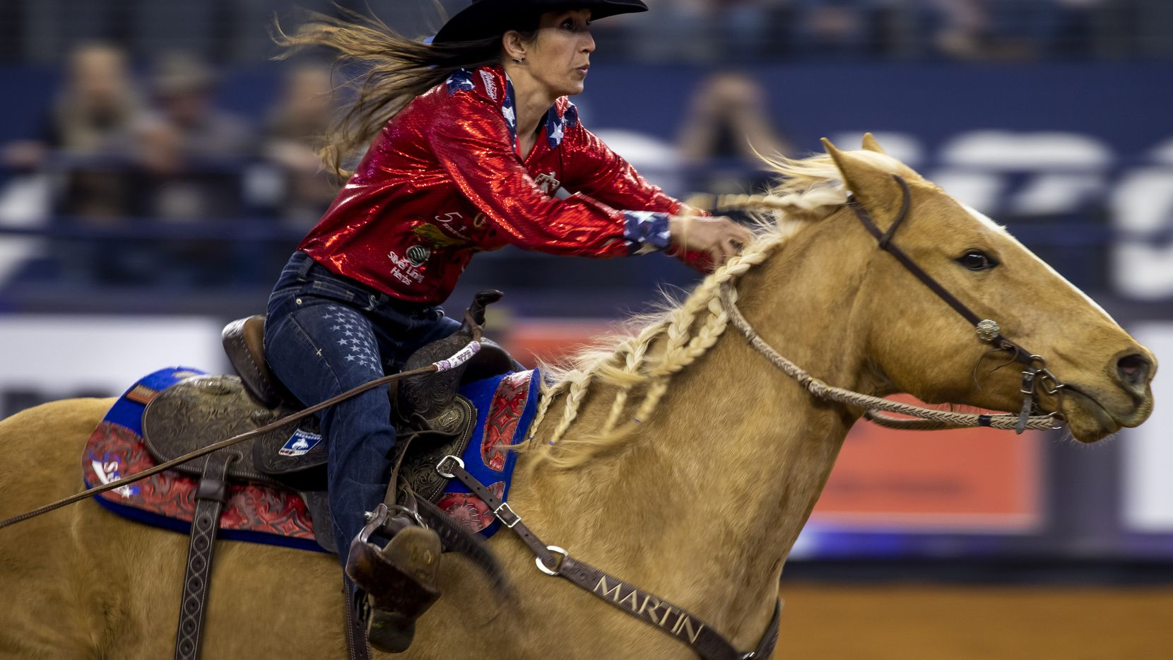 A rodeo rider competes in barrel racing.
