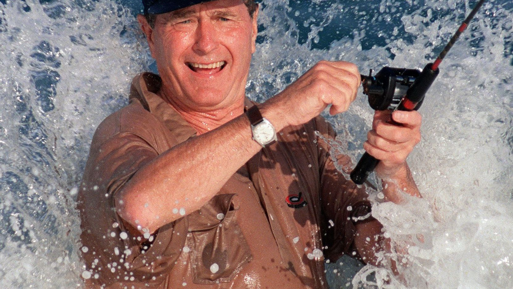 (FILES) In this file photo taken on November 14, 1988 President elect George Bush is smashed by a wave 14 November 1988 while fishing in back of the home of William Farish in Florida. (Photo by Roberto SULLIVAN / AFP)
