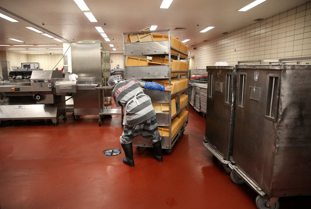 An inmate moves a cart of trays for meal prep in the kitchen at the Lew Sterrett Justice Center in Dallas. The trusty inmates prepare food for the Dallas County adult and juvenile facilities.