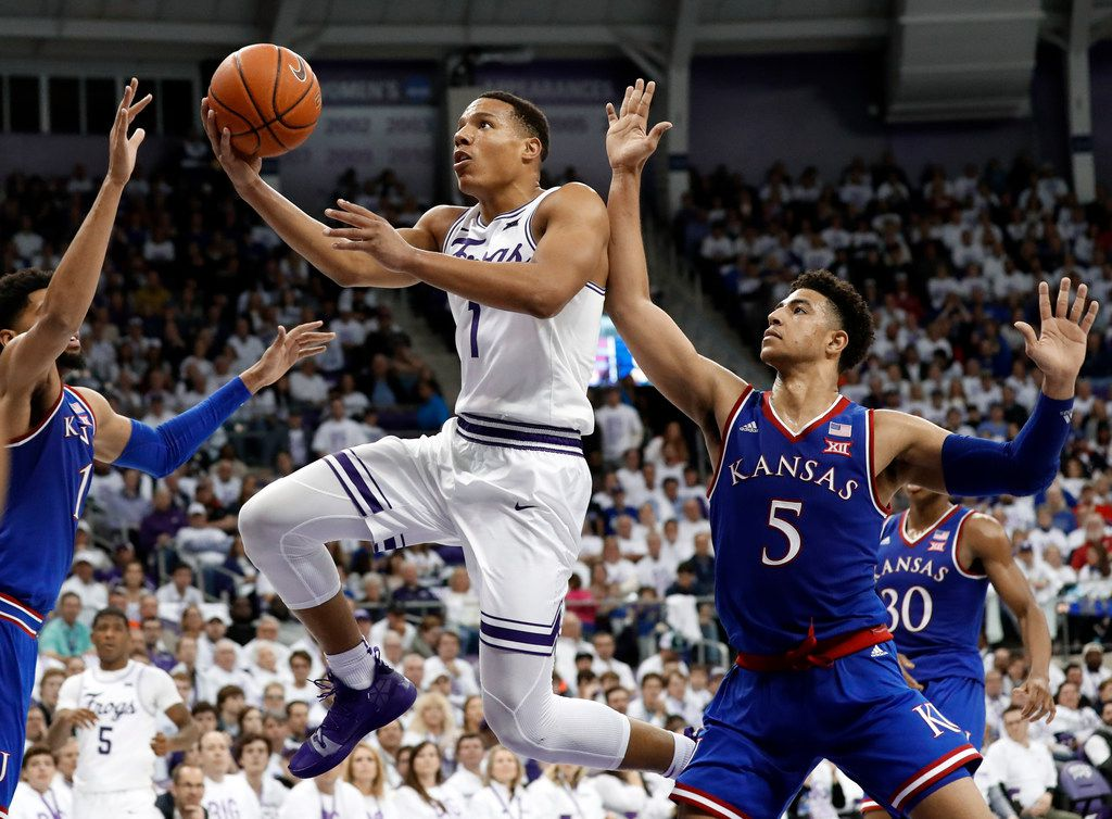 Kansas forward Dedric Lawson (1) and guard Quentin Grimes (5) defend as TCU guard Desmond Bane (1) leaps to the basket for a shot in the second half of an NCAA college basketball game in Fort Worth, Texas, Monday, Feb. 11, 2019. (AP Photo/Tony Gutierrez)