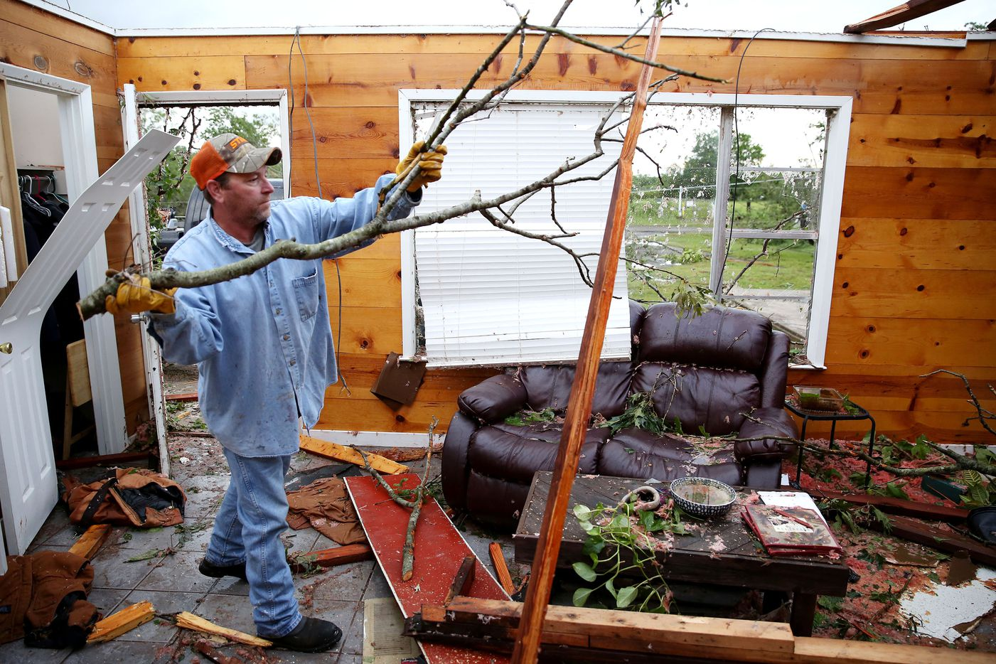 Andy Teague cleans up the living room of his family home along County Road 1910 after a tornado impacted Fruitvale, Texas on Sunday April 30, 2017. Teague took shelter in a tiled-shower with his wife Amy Teague, daughter Shelbie Teague, Shelbie's boyfriend Brandon Sherwood and two dogs. (Andy Jacobsohn/The Dallas Morning News)