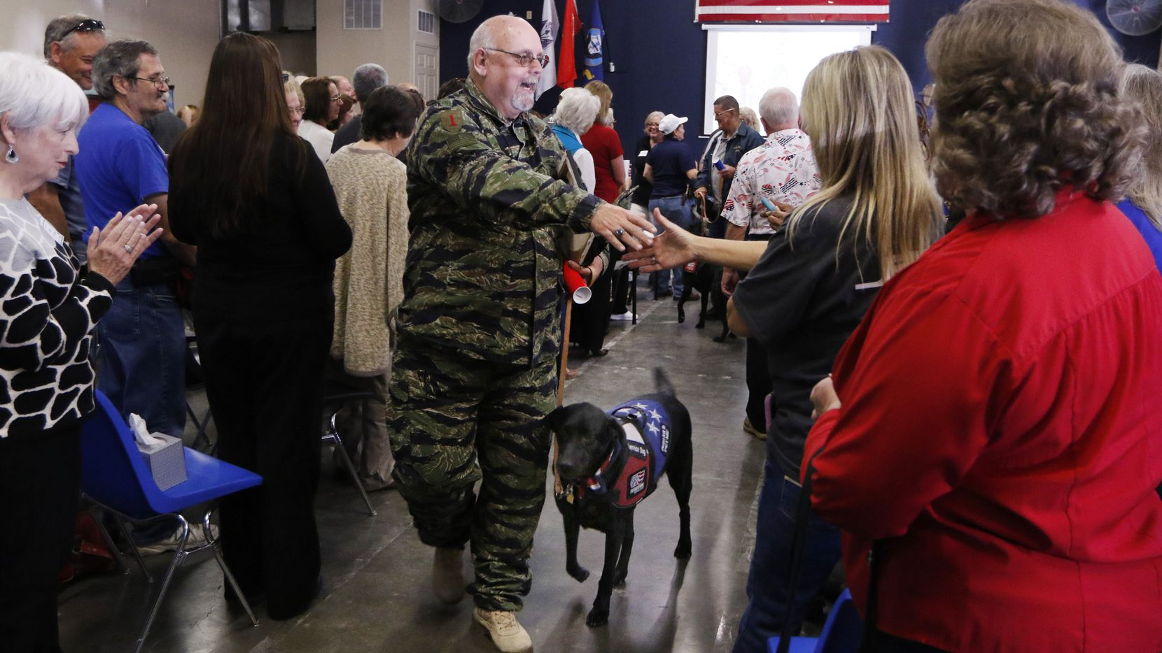 Jay Springstead, U.S. Army 1st Ltd. and his new service dog, Tex, greets people after he and four other veterans received service dogs from ParriotPAWS Service Dogs on Friday, November 11, 2016 in Rockwall, Texas. Parriot PAWS Service Dogs have placed 120 dogs over ten years. (David Woo/The Dallas Morning News)