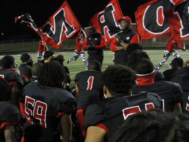 Cedar Hill head coach Carlos Lynn shares a congratulatory message to his team as members of the Red Army Flag Runners sprint past in the background following the Longhorn's 49-42 victory over DeSoto. The two teams played their District 11-6A  football game at Longhorn Stadium in Cedar Hill on November 6, 2020.