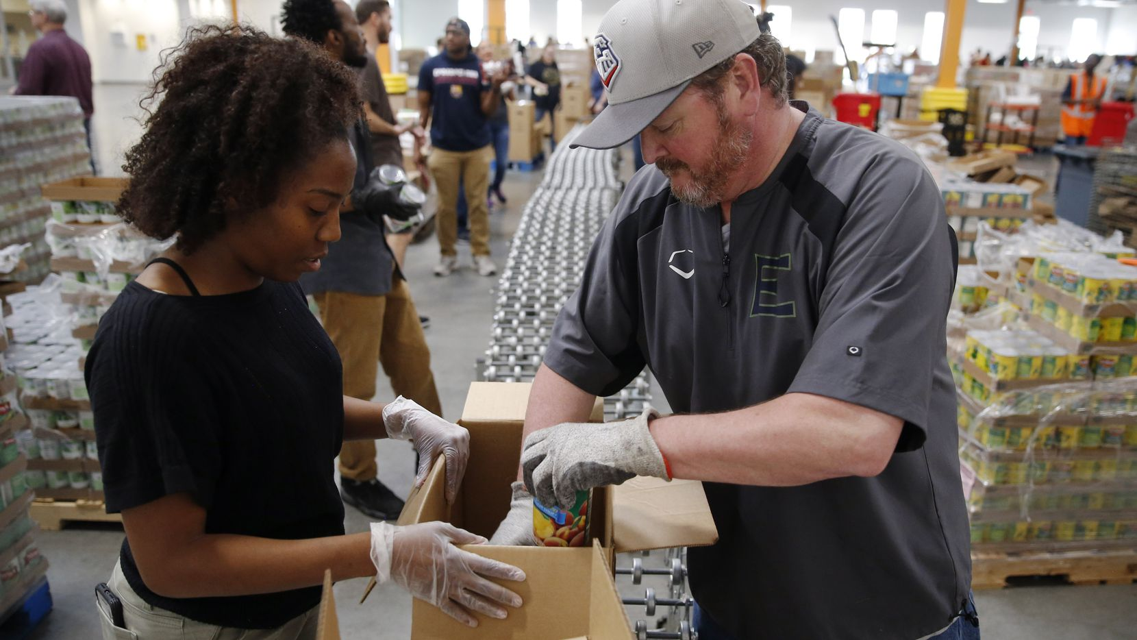 Tatyana Lowery (left) of Dallas  and Mark Martin (right) of Rowlett work on putting together boxes for distribution.