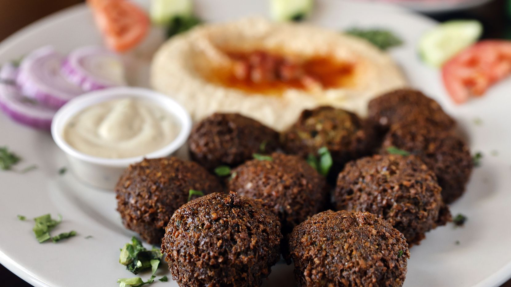 The falafel plate served with homemade hummus made with chickpeas and topped with paprika is served at Aladdin Mediterranean Cafe in Fort Worth.