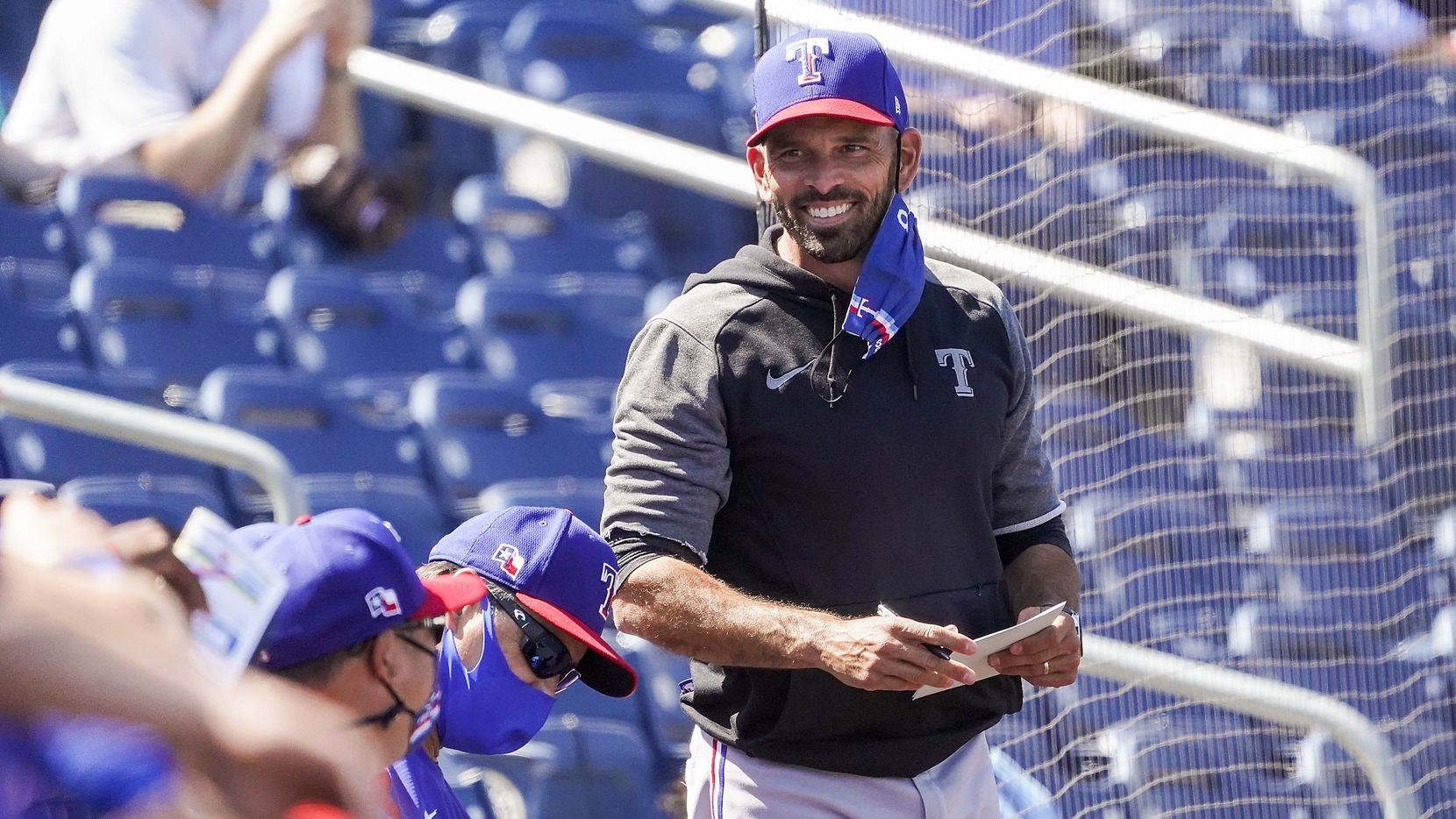 Texas Rangers manager Chris Woodward smiles as he watches during the first inning of a spring training game against the Seattle Mariners at Peoria Sports Complex on Wednesday, March 10, 2021, in Peoria, Ariz.