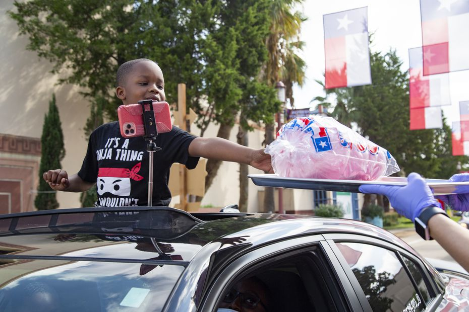 Jaeden Beaty, 8, reaches out for cotton candy at the Big Tex Fair Food Drive-Thru at Fair Park in Dallas on Friday, Sept. 25, 2020.
