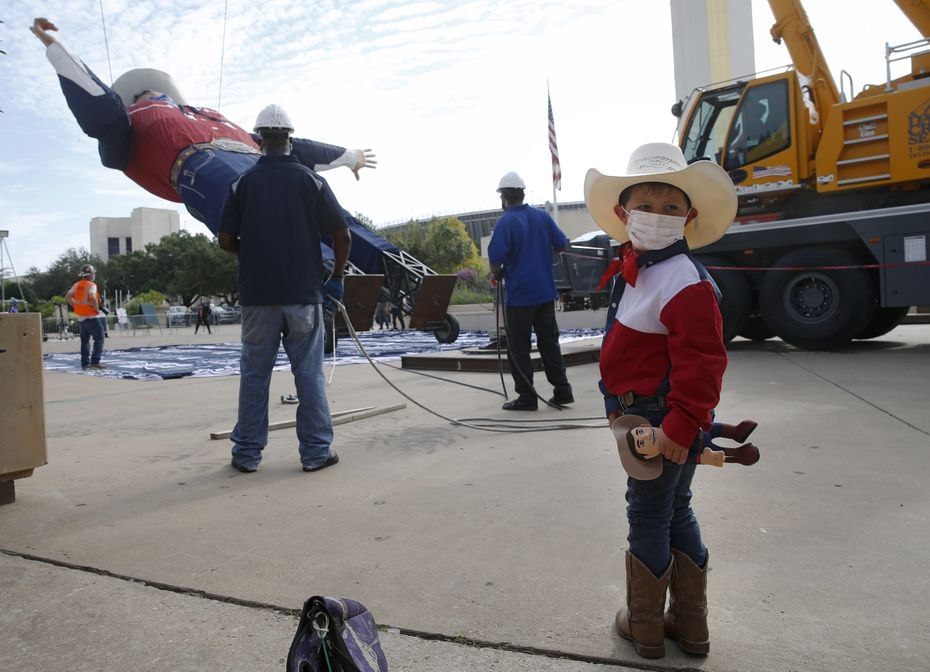 Jeffry Carter, 4 of Colleyville, is all in on Dallas' tall cowboy: Carter is holding a tiny Big Tex doll, dressed as Big Tex, watching the Big Tex installation.