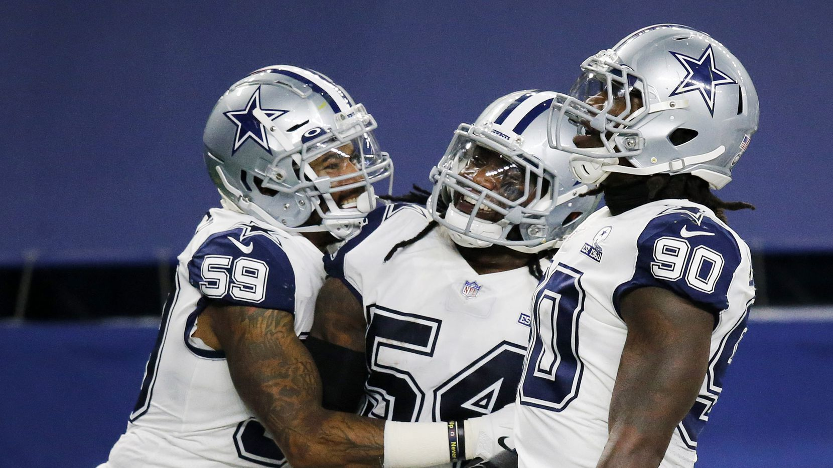 Dallas Cowboys middle linebacker Jaylon Smith (54) is congratulated on his third quarter interception return by linebacker Justin March (59) and defensive end DeMarcus Lawrence (90) at AT&T Stadium in Arlington, Thursday, November 26, 2020. He almost scored a touchdown.