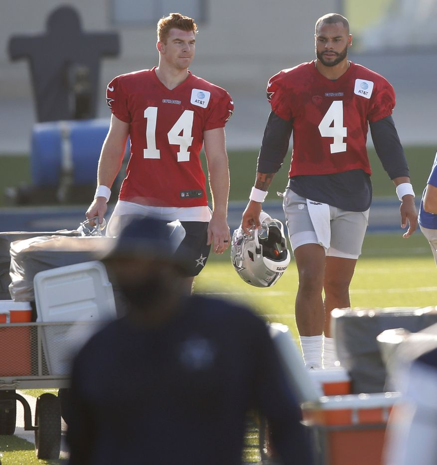 Dallas Cowboys quarterback Andy Dalton (14) and Dallas Cowboys quarterback Dak Prescott (4) take the field for practice during the first day of training camp at Dallas Cowboys headquarters at The Star in Frisco, Texas on Friday, August 14, 2020. (Vernon Bryant/The Dallas Morning News)
