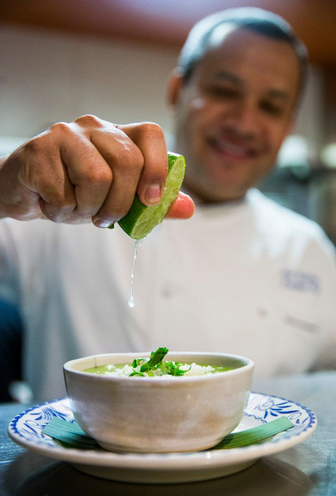 Chef Nico Sanchez squeezes lime juice on top of a bowl of his pozole verde at Mesa Maya.