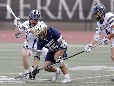 Dallas Jesuit's Sam Teachout (15) scoops up the ball between Highland Park's Mason Gallas, left, and Hayden Helgemoe (4) during the Class AA Texas High School Lacrosse League State Championship game held at George Turner Stadium in Humble, Texas on Sunday, May 9, 2021. (Michael Wyke/Special Contributor)