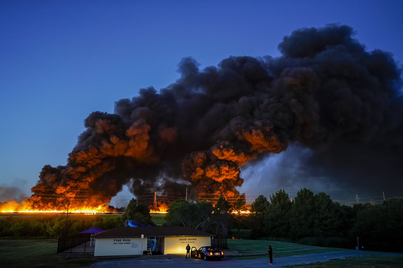 A plume of smoke rises over people gathered in Tyre Park to watch fire crews battle a massive blaze in an industrial area of Grand Prairie, in the early morning hours of Wednesday, Aug. 19, 2020.