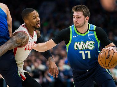 Dallas Mavericks forward Luka Doncic (77) is defended by Portland Trail Blazers guard Damian Lillard (0) during the first quarter of an NBA game between the Dallas Mavericks and the Portland Trail Blazers on Friday, January 17, 2020 at American Airlines Center in Dallas.