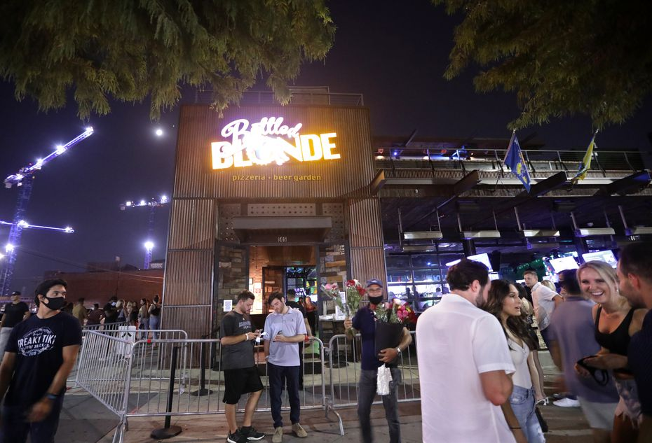 People gather outside Bottled Blonde in the Deep Ellum area of Dallas on Aug. 28, 2020. Soon after, a TABC investigation was closed and the bar was not cited. A TABC spokesman says agents continue to monitor all bars across the state, even after an investigation is closed.