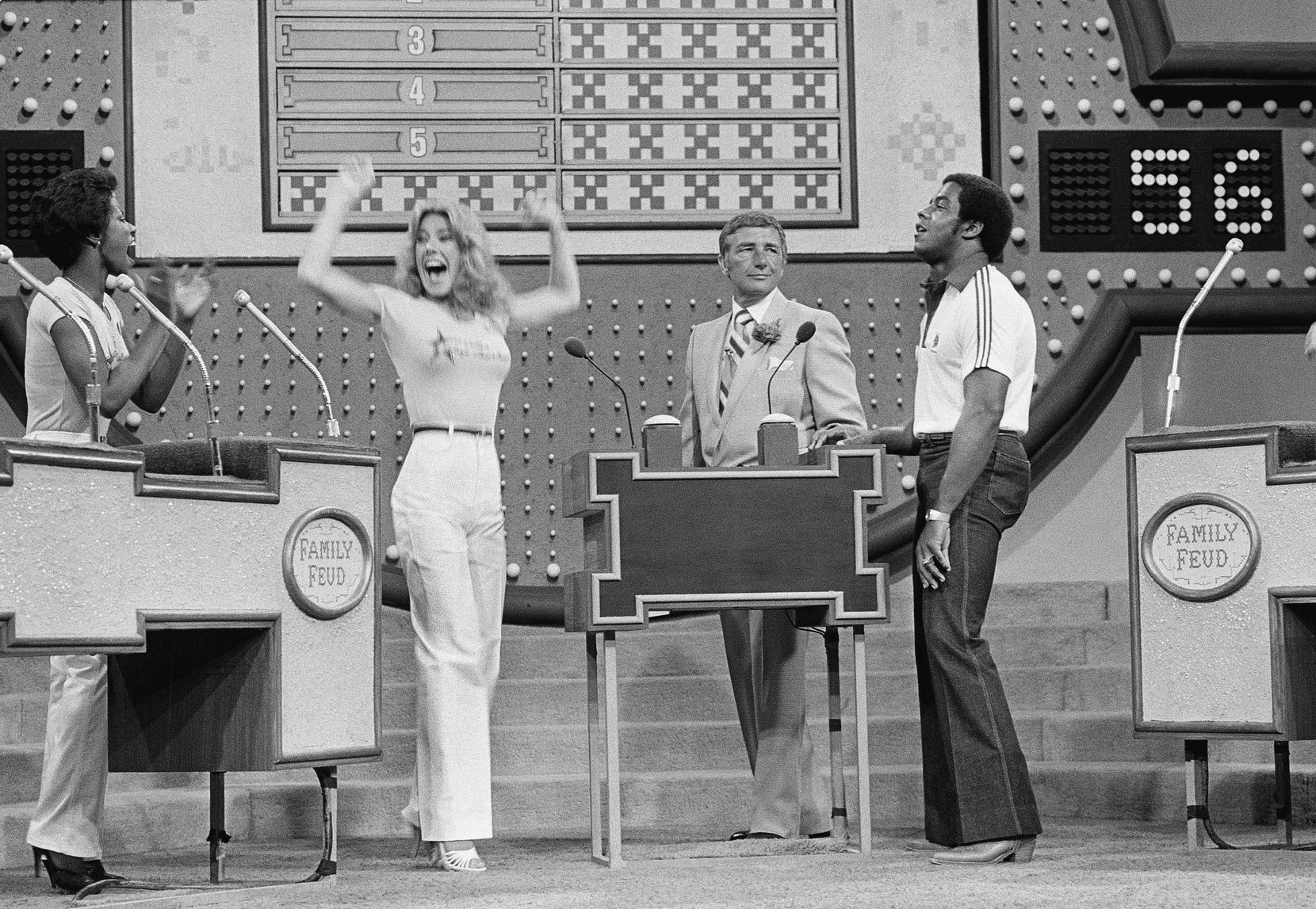 In this June 25, 1980 file photo, host Richard Dawson, center, watches while Dallas Cowboys running back Tony Dorsett, right, grimaces and Cowboys cheerleader Suzette Scholz-Derrick waves happily.
