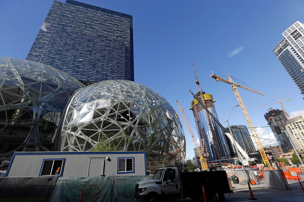 In this Wednesday, Oct. 11, 2017, photo, large spheres take shape in front of an existing Amazon building, behind, as new construction continues across the street in Seattle. Memo to the many places vying for Amazon's second headquarters: It ain't all food trucks and free bananas. For years now, much of downtown Seattle has been a maze of broken streets and caution-taped sidewalks, with dozens of enormous cranes towering overhead as construction trucks rumble past pedestrians and bicyclists. And while Amazon is far from solely to blame for these issues, and many say the benefits clearly outweigh the drawbacks, life has been disrupted.