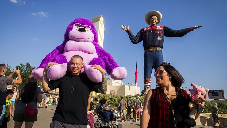 Jason Chiaruttini of Houston carries a stuffed animal won on the midway past Big Tex on a visit to the State Fair of Texas on the first weekend day of the fair, Saturday, Sept. 26, 2015, in Dallas.