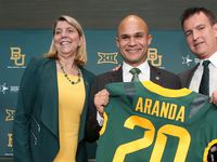 Baylor University Dr. Linda A. Livingstone, left, and Athletic Director Mack Rhoades, right, present new head football coach Dave Aranda, center, with a jersey during an during an NCAA college football news conference, Monday, Jan. 20, 2020, in Waco, Texas.