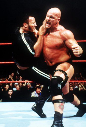 Smackdown!  Stone Cold Steve Austin (right) puts down an opponent.