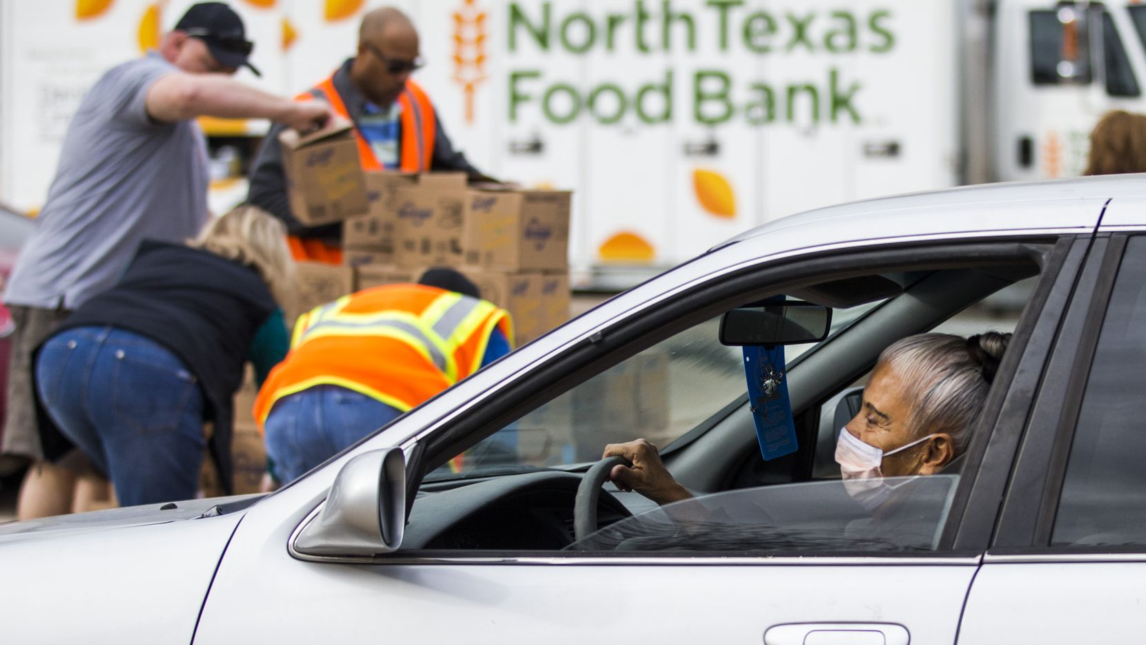 A woman wearing a surgical mask drives past volunteers who prepare to hand out boxes of food to families in vehicles. The North Texas Food Bank is currently leading a peanut butter drive that aims to raise 300,000 pounds of peanut butter to benefit local food banks.