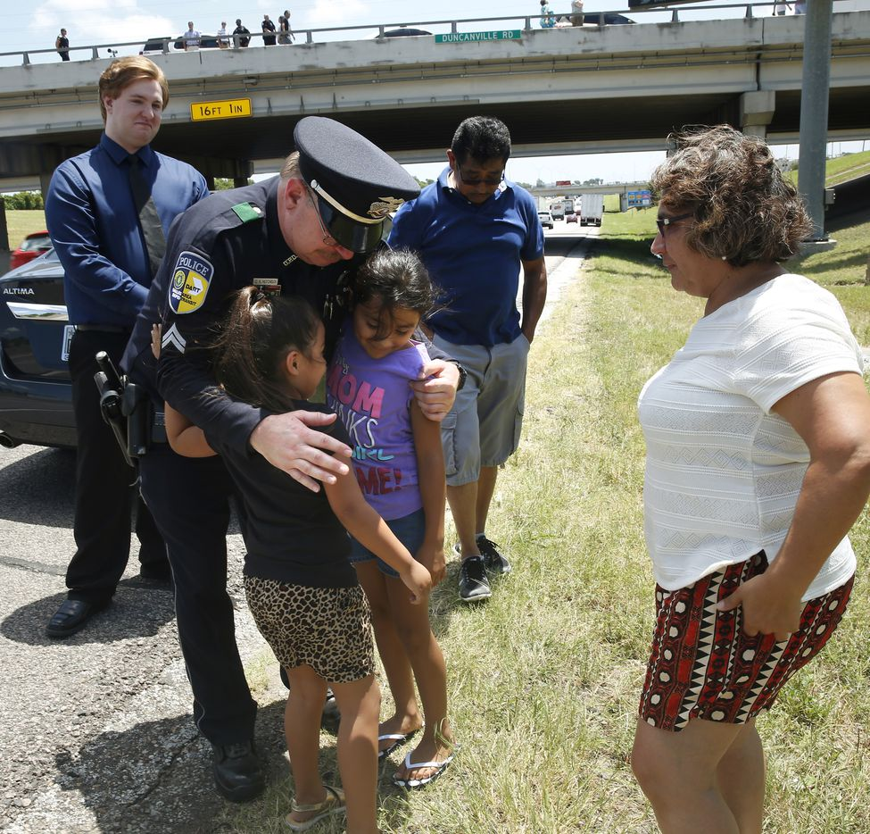 DART Corporal Gary Hutchison is hugged by Jasmine Castro, 9, (left) and Isabella Castro, 9, as their parents Marino and Beatrice Castro watch on after the funeral procession for DART Officer Brent Thompson on Interstate 20 in Duncanville, Texas on Wednesday, July 13, 2016. Thompson and four other officers were killed during an attack during a peaceful Black Lives Matter protest on July 7, 2016.