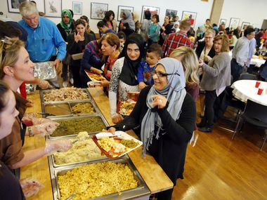 Iraqi refugee Shukriyah Merza (right) thanks volunteers for her meal during the 6th annual Thanksgiving With Refugees dinner at St. John's Episcopal Church in Dallas Nov. 24, 2016.