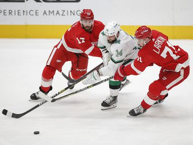 Dallas Stars forward Jamie Benn (14) battles Detroit Red Wings defenseman Filip Hronek (17) and  forward Dylan Larkin (71) for space  during the second period of an NHL hockey game in Dallas, Monday, April 19, 2021.