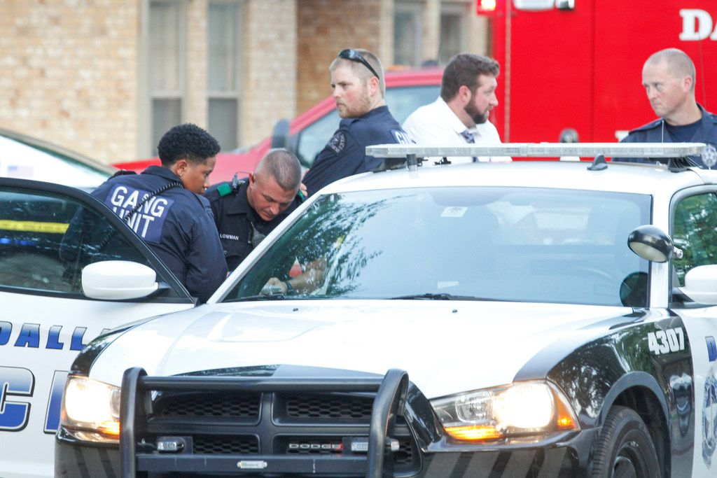 Members of Dallas Police Department gang unit spoke to a person in a squad car at the Roseland Town Homes after a  9-year-old girl was fatally shot Wednesday. Dallas police said the shooting was gang-related