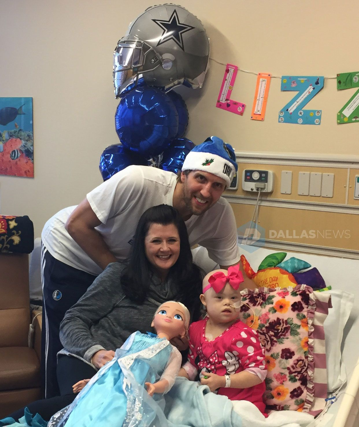 Dirk Nowitzki poses with patient Lizzy Hock, 4, and her mother Angela Hock, at Children's Medical Center after giving Lizzy and Elsa doll for Christmas.