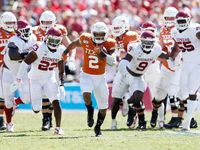 Texas Longhorns quarterback Roschon Johnson (2) runs up the field for a big play as Oklahoma Sooners defense chases after him during the second half of play in the Red River Showdown at the Cotton Bowl in Dallas on Saturday, October 12, 2019.