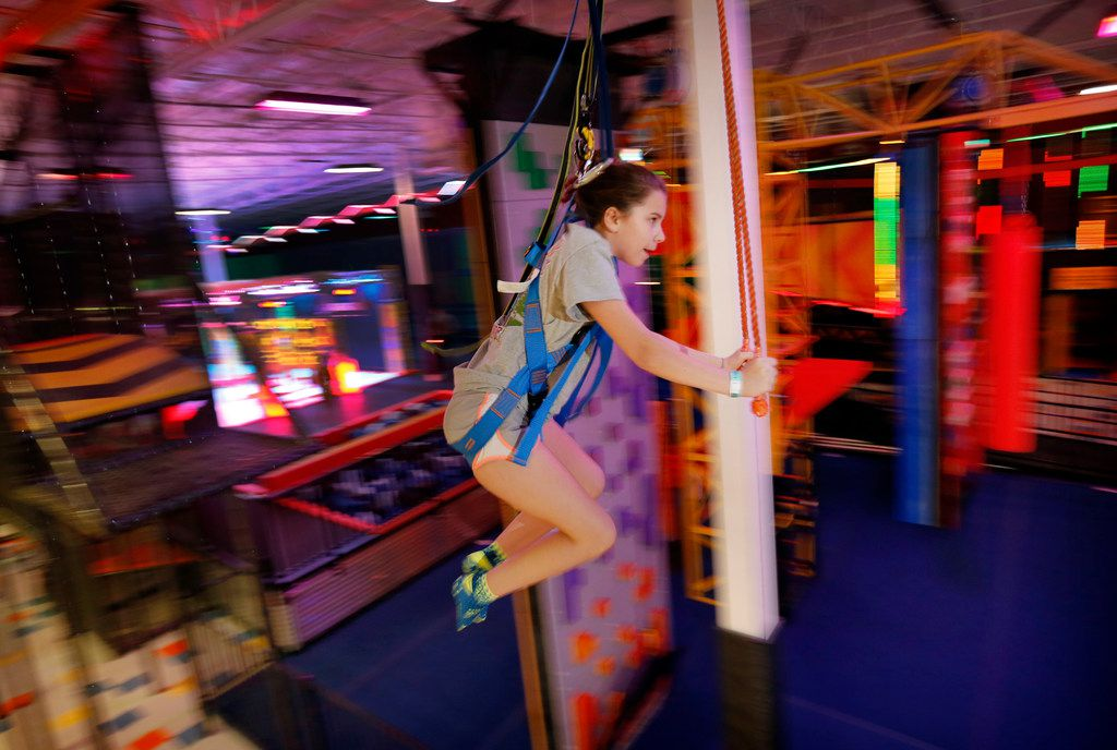 Ainsley Alexander, 11, of Grapevine is a blur as she rides the Sky Rider track around the top of Urban Air Adventure Park's flagship location in Southlake.
