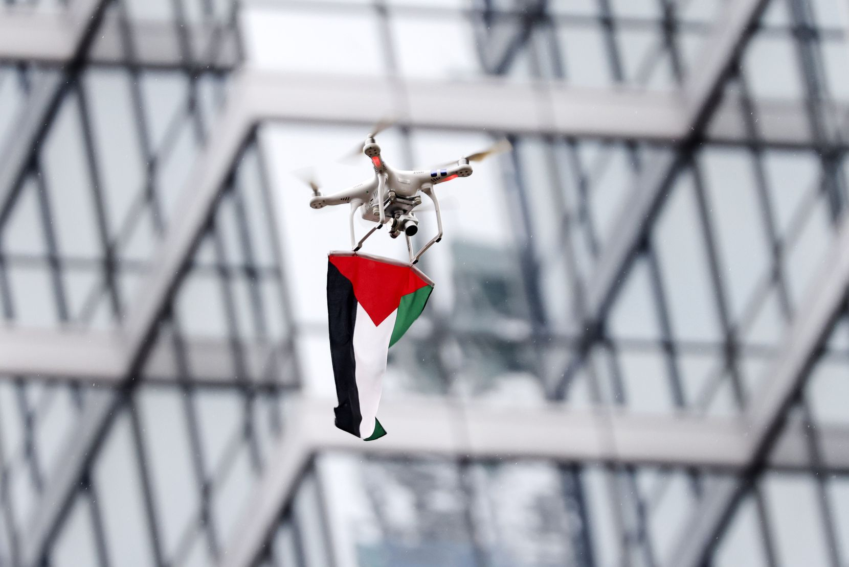 A drone carrying a Palestinian flag hovers over Belo Garden during the rally.