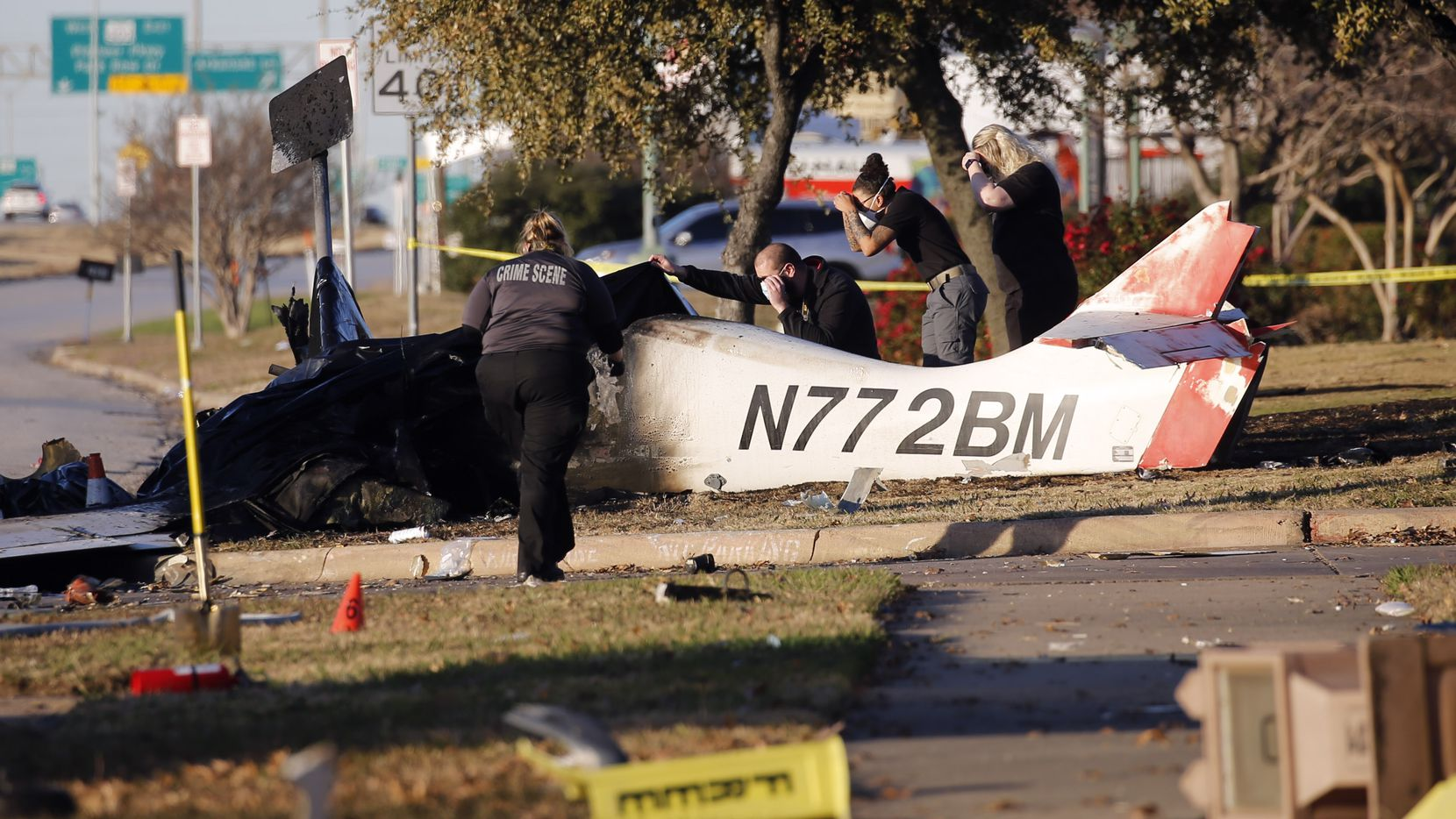 Officials look at the scene of a fatal plane crash near the intersection of Mayfield Road and Highway 360 on Monday, December 21, 2020 in Grand Prairie, Texas.  (Vernon Bryant/The Dallas Morning News)