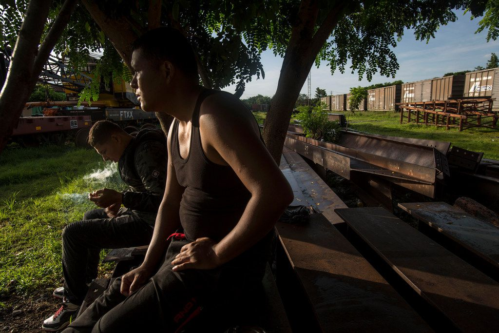 Honduran migrants sit on discarded rail tracks as they wait for a train heading north, in Arriaga, Mexico, on June 24, 2019. Mexican authorities are reinforcing efforts to deter Central Americans and others from crossing the country to reach the United States, detaining migrants in the south and stationing National Guardsmen along the Rio Grande in the north.