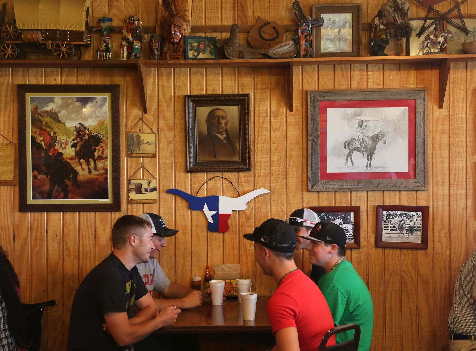 Diners eat at Kirby's Barbeque in Mexia. Some of the photos depict the life of Comanche chief Quanah Parker, whose mother Cynthia Ann Parker was kidnapped during the raid of Fort Parker, which is right outside Mexia.