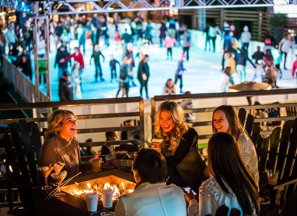 Guests stay warm by a firepit at the Cosmopolitan Resort's rooftop deck, where the resort pool becomes an ice skating rink with a bird's-eye view of the Las Vegas Strip.