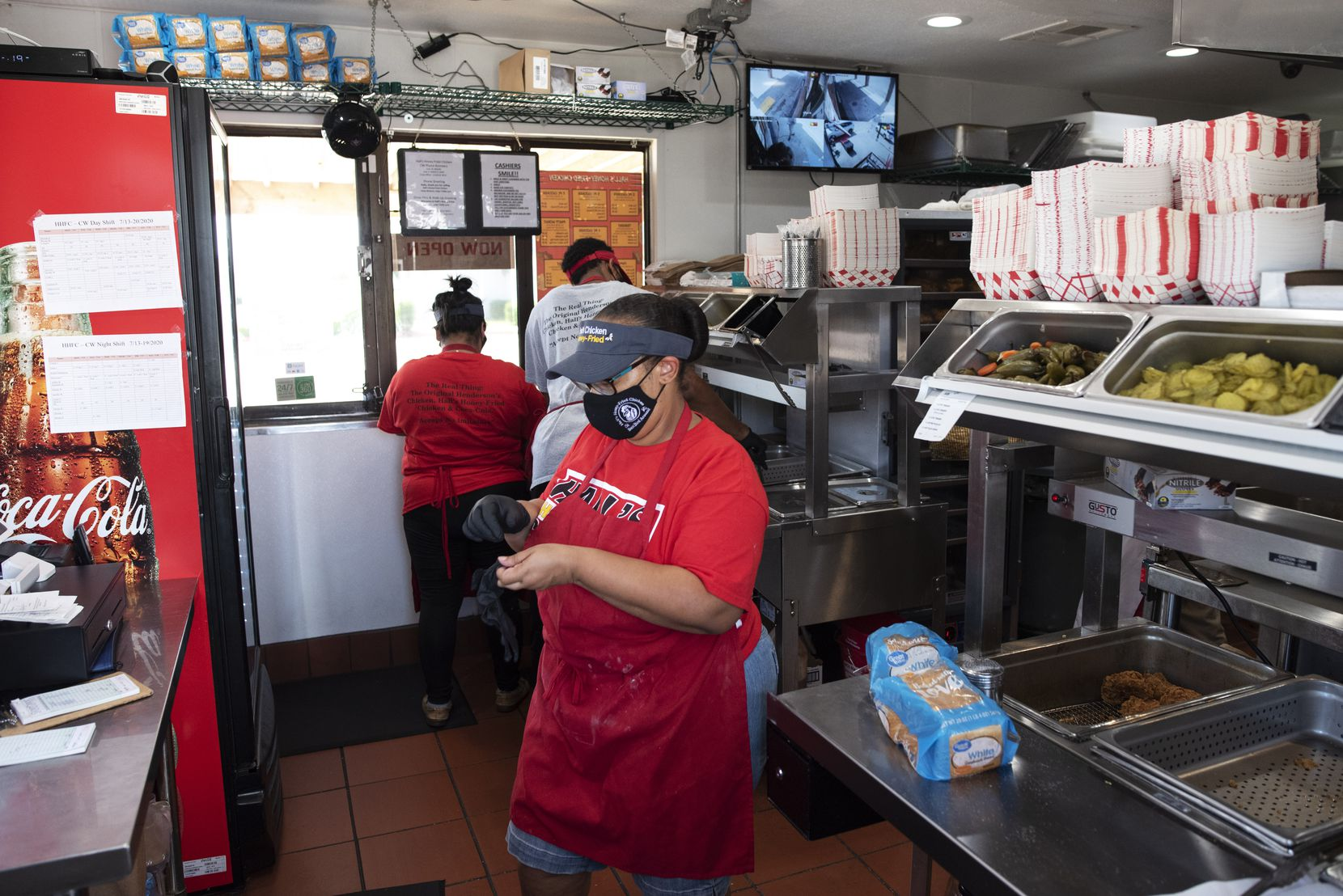 Employees prepare food orders inside the reopened Hall's Honey Fried Chicken on West Camp Wisdom Road in Dallas