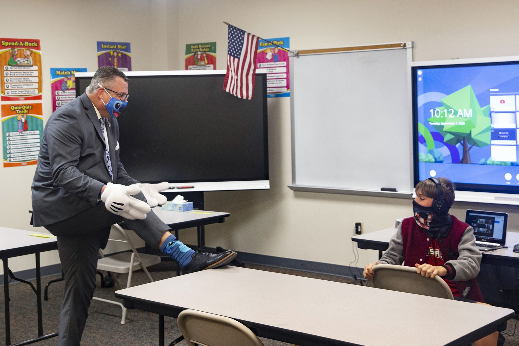 Superintendent Dr. Michael Goddard (left) shows off his playful socks to sixth-grade student Major Morris during a visit to employee children at Carrie L. Lovejoy Elementary School in Allen on Sept. 1. The district provided in-person child care and instruction for the children of some district employees who had to physically report to work at the beginning of the school year during the coronavirus pandemic.