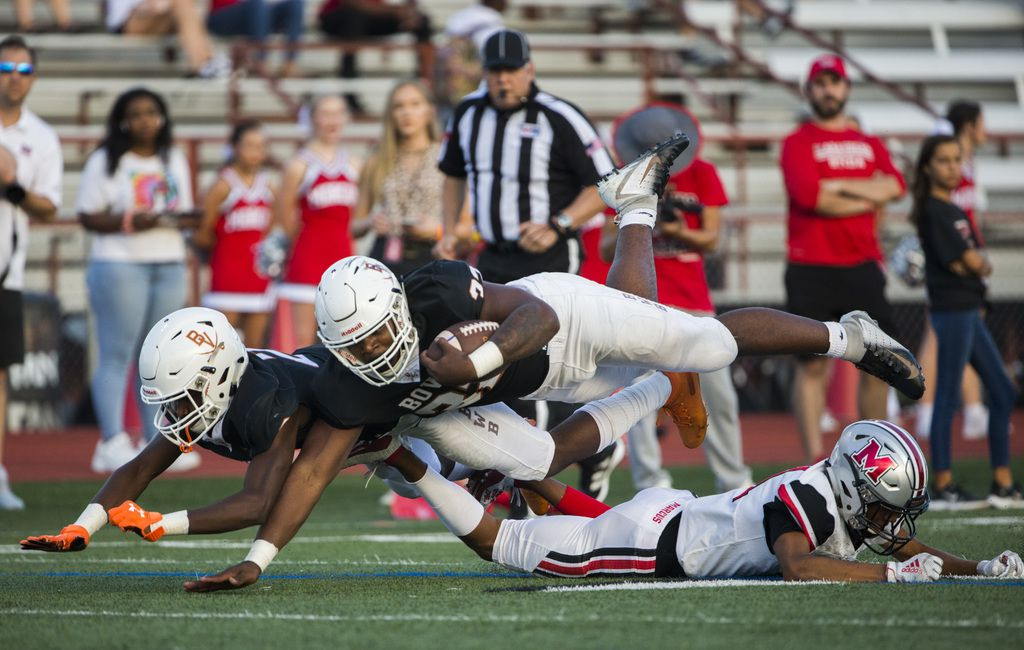 Arlington Bowie running back Marsaillus Sims (32) and wide receiver Paul Alexander (2) are tripped up by Flower Mound Marcus defensive back Zach Morris (21) during the first quarter of a high school football game between Flower Mound Marcus and Arlington Bowie on Thursday, August 29, 2019 at Wilemon Field in Arlington. (Ashley Landis/The Dallas Morning News)