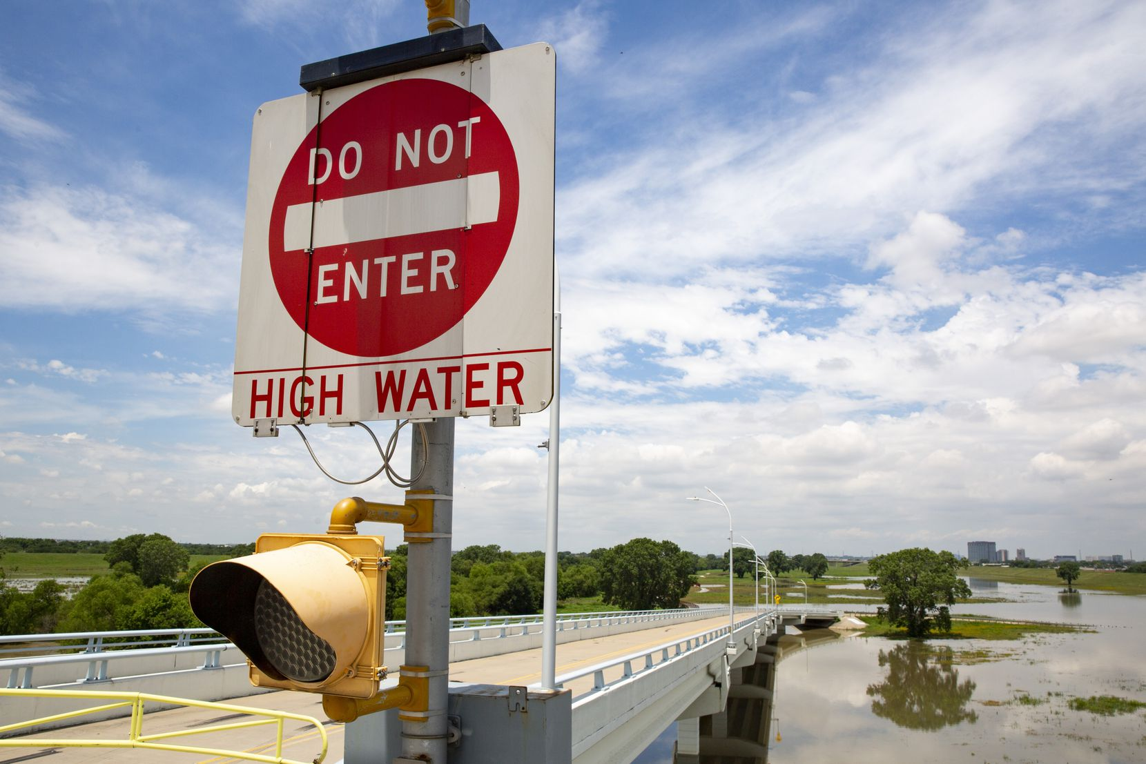 A closed sign on the road to Trammell Crow Park warning of high water from the Trinity River on Wednesday, June 2, 2021, in Dallas.