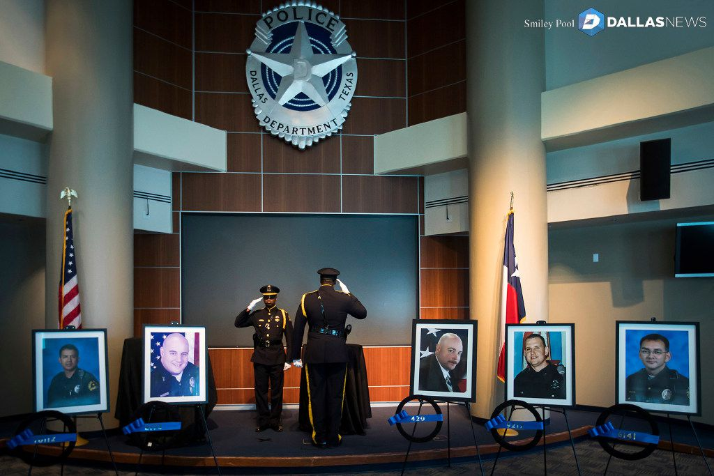 Police Sgt. Michael Bables (left) saluted Officer Londrell Tatum as Tatum took his post beside the United States Honor Flag at Dallas police headquarters on July 8, 2017.