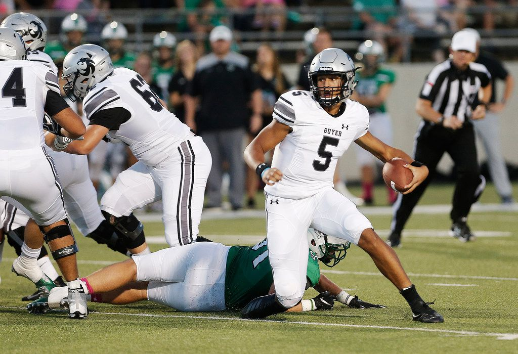 Denton Guyer sophomore quarterback Eli Stowers (5) evades a sack from Southlake Carroll junior defensive lineman Dillon Springer (91) during the first half of a high school football game at Dragon Stadium in Southlake, Friday, October 5, 2018. (Brandon Wade/Special Contributor)