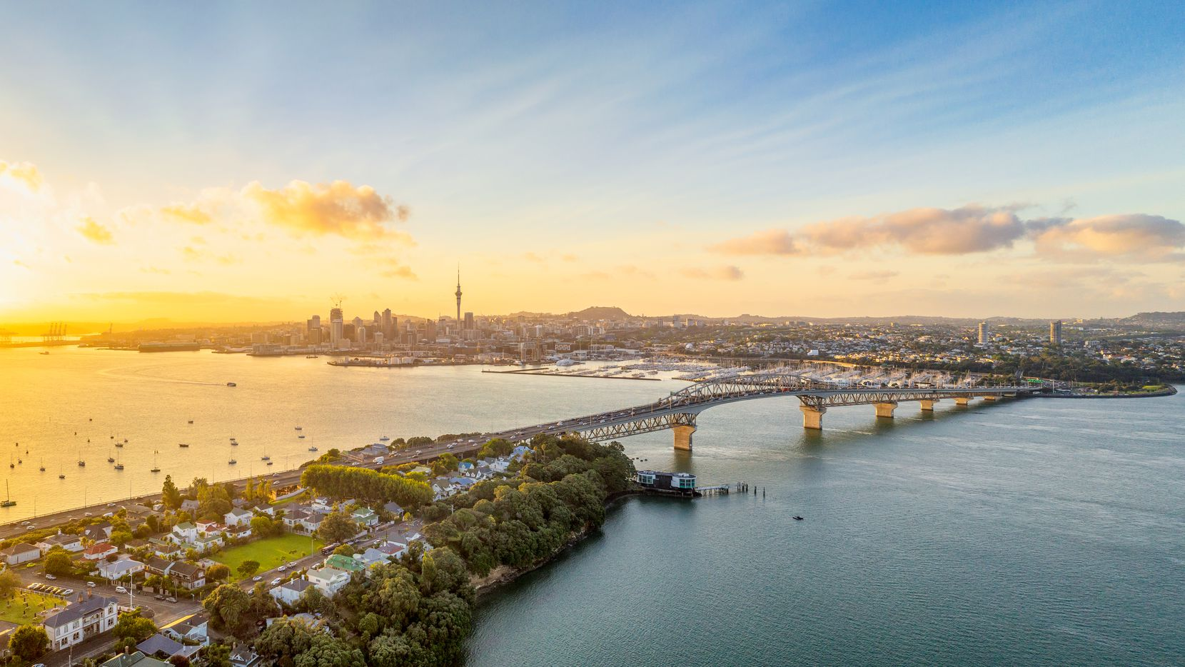 A panoramic image from above of Auckland, with the Sky Tower and CBD visible across Waitemata Harbor and the Auckland Harbour Bridge. American will start flying to the New Zealand city in October 2020.