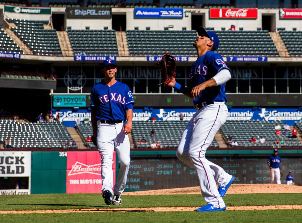Texas Rangers first baseman Ronald Guzman (11) looks up at a ball hit by Boston Red Sox short stop Chris Owings (36) that was thrown by starting pitcher Mike Minor (23, left) during the ninth inning of an MLB game between the Boston Red Sox and the Texas Rangers on Thursday, September 26, 2019 at Globe Life Park in Arlington. Guzman did not catch the ball.