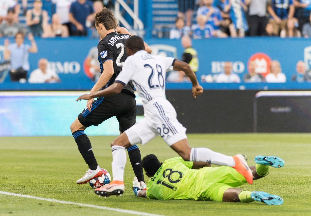 Montreal Impact's Lassi Lappalainen, left, scores against Philadelphia Union's goalkeeper Andre Blake (18) as Union's Raymon Gaddis (28) defends during the first half of an MLS soccer game, Saturday, July 27, 2019 in Montreal. (Graham Hughes/The Canadian Press via AP)