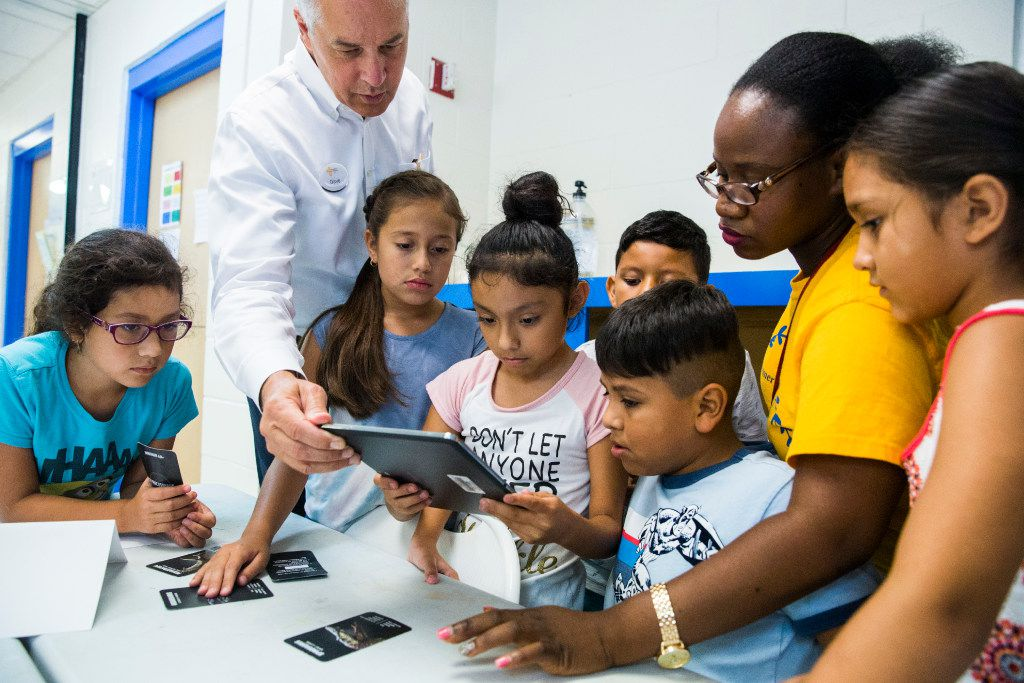 CEO Dave Woodyard, second from left, helps third graders with a 4D dinosaur tablet activity during a Catholic Charities of Dallas summer camp on Monday, July 10, 2017 at the Cardinal Farrell Community Center, in Dallas. (Ashley Landis/The Dallas Morning News)