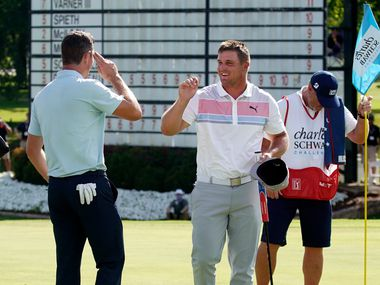 PGA Tour golfer Justin Rose salutes playing partner Bryson DeChambeau who gave him an air high-five after their second round of the Charles Schwab Challenge at the Colonial Country Club in Fort Worth, Friday, June 12, 2020.