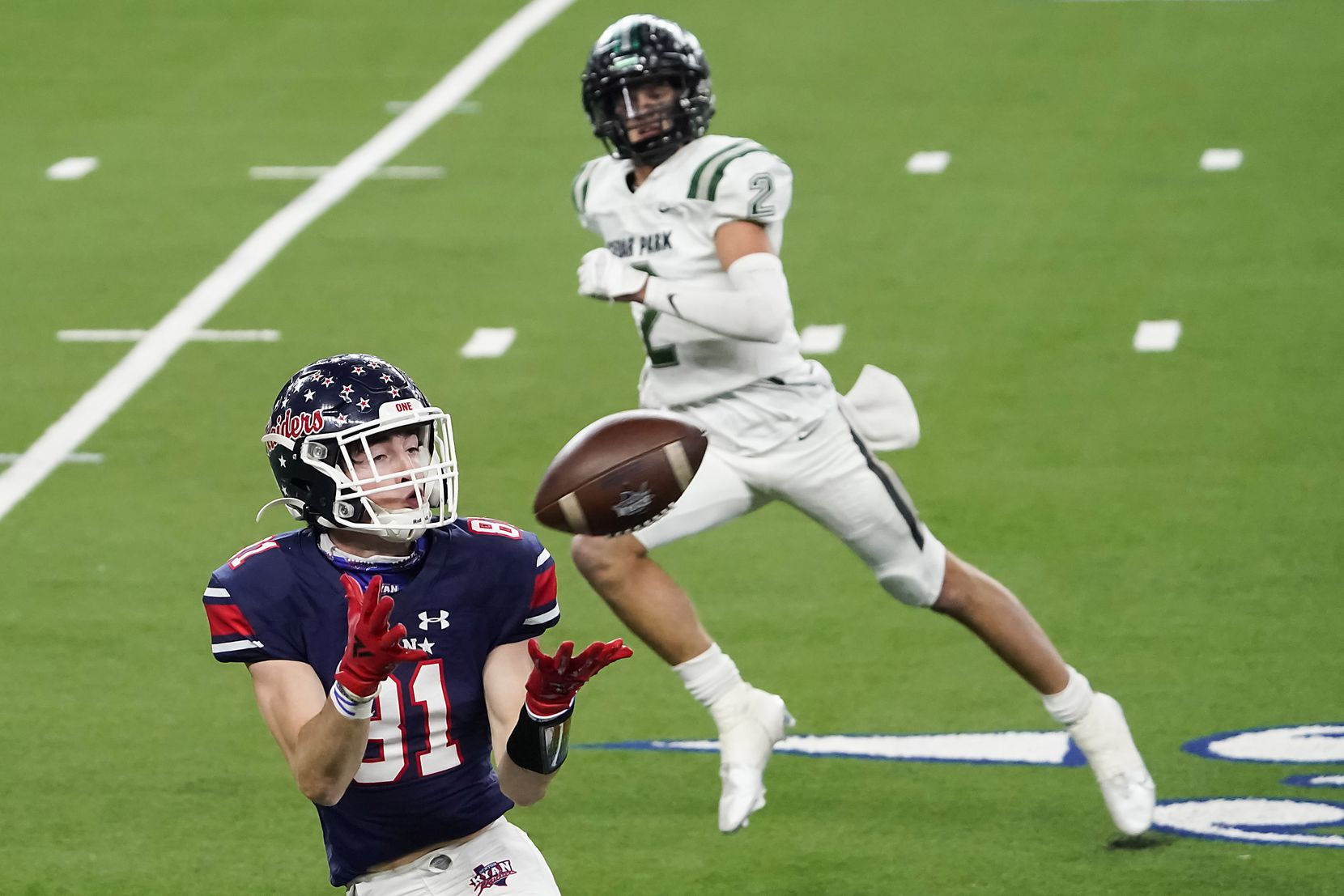 Denton Ryan wide receiver Keagan Cunningham (81) hauls in a 52-yard touchdown pass from quarterback Seth Henigan as Cedar Park defensive back Blake Burton (2) defends during the first half of the Class 5A Division I state football championship game at AT&T Stadium on Friday, Jan. 15, 2021, in Arlington, Texas. (Smiley N. Pool/The Dallas Morning News)